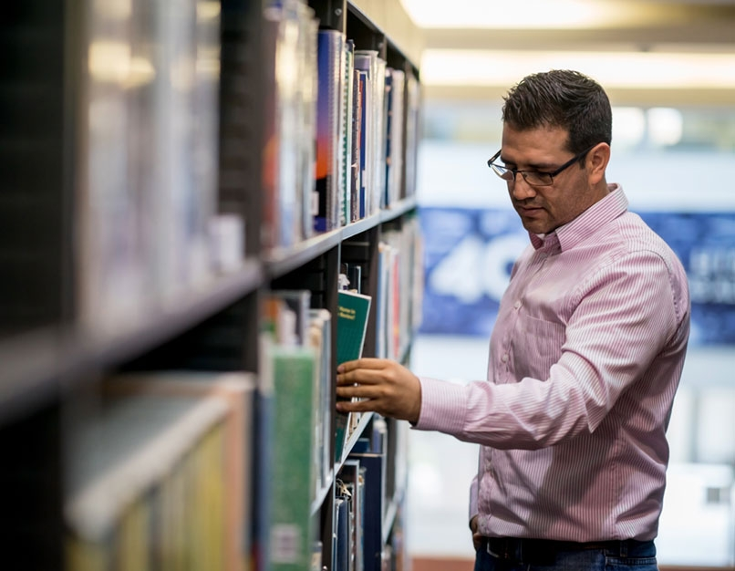 individual in library, searching for book