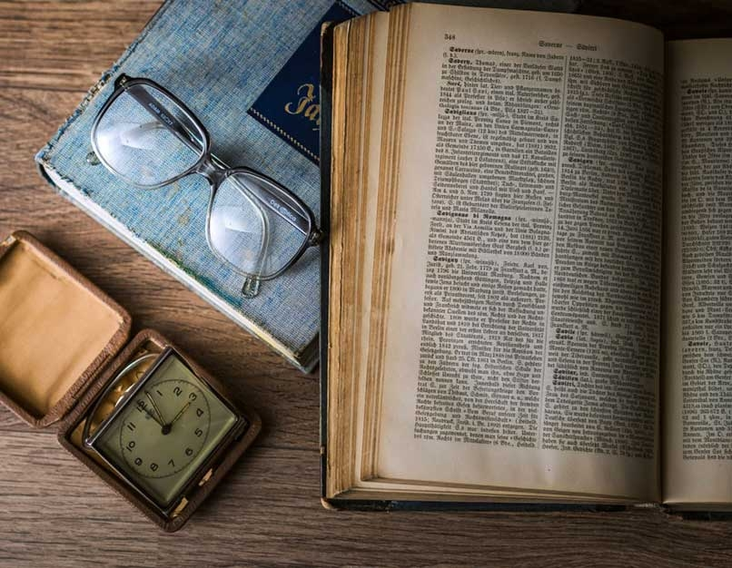 open book, glasses, clock