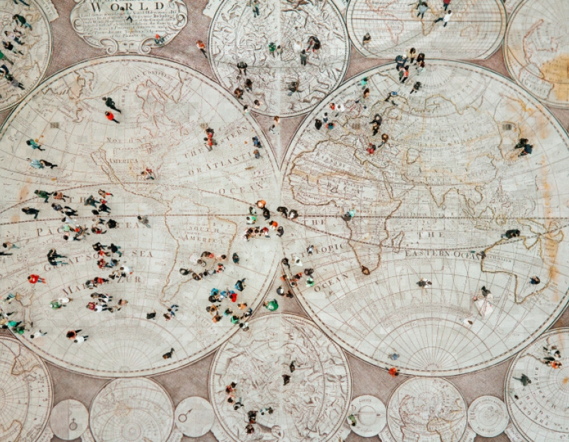 Aerial view of a crowd walking on an antique global map