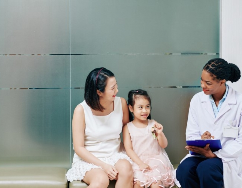 A family nurse practitioner sits with a parent and child.