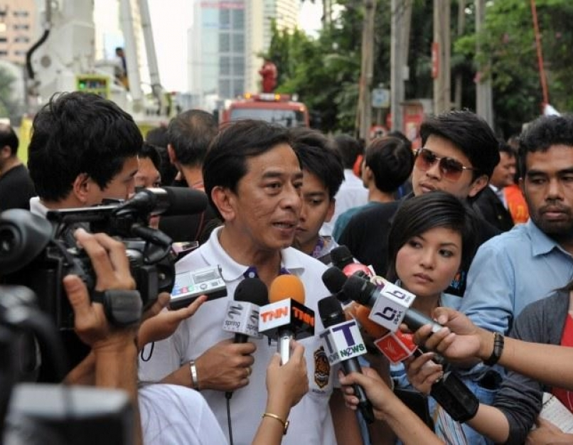 A large group of journalists holding out microphones interview a Thai government official on the street.