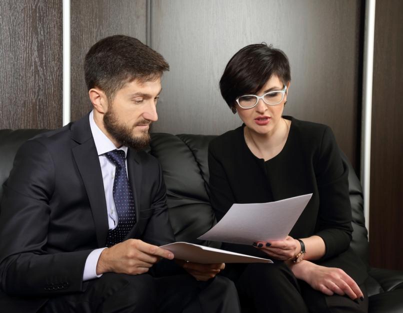 Two government contract managers review a set of documents.